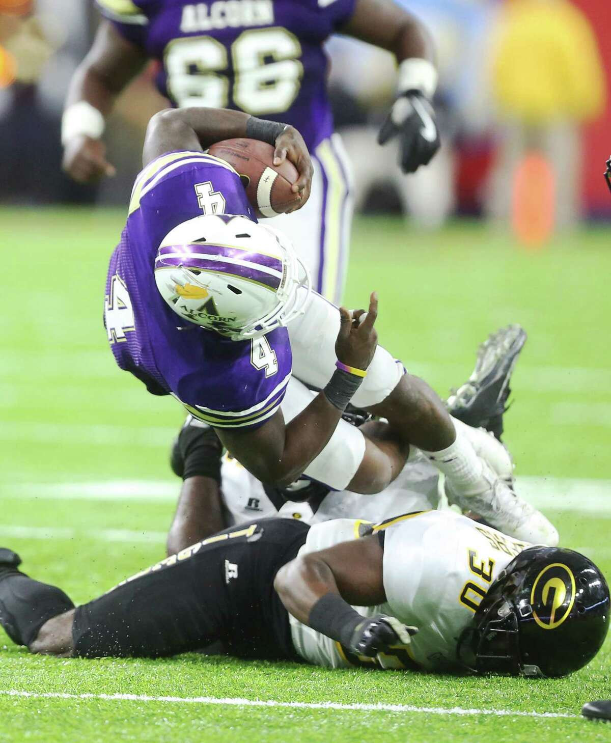 Alcorn State University running back Silas Spearman (4) leaps in the air to dodge the tackle from Grambling State University's Derrick Dixon (30) during the first half of the Southwestern Athletic Conference Championship Game at NRG Stadium Saturday, Dec. 3, 2016, in Houston.