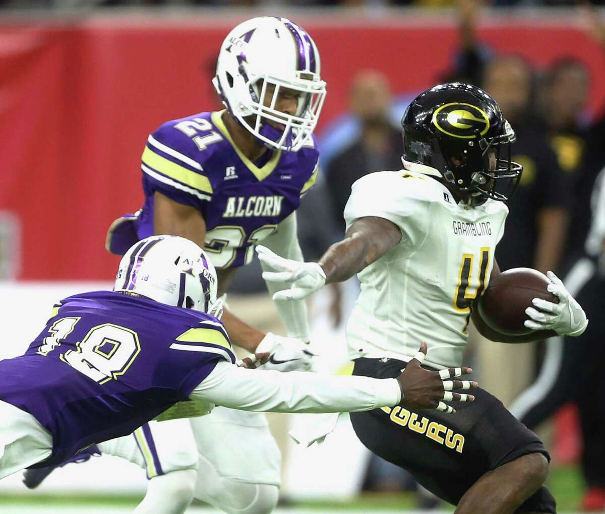 Grambling State University's Martez Carter (4) is tackled by Alcorn State University's Leishaun Ealey (18) and Jayron Harness (21) during the first quarter of Southwestern Athletic Conference Championship Game at NRG Stadium Saturday, Dec. 3, 2016, in Houston.