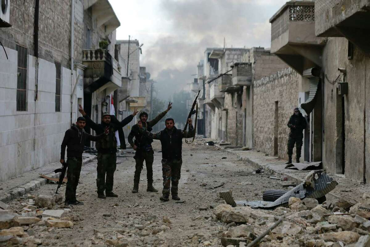 Syrian army soldiers flash the V for Victory-sign as they patrol the east Aleppo neighborhood of Tariq al-Bab, Syria, Saturday, Dec. 3, 2016. Tariq al-Bab was captured by Syrian government forces on Friday. (AP Photo/Hassan Ammar) ORG XMIT: HAS104