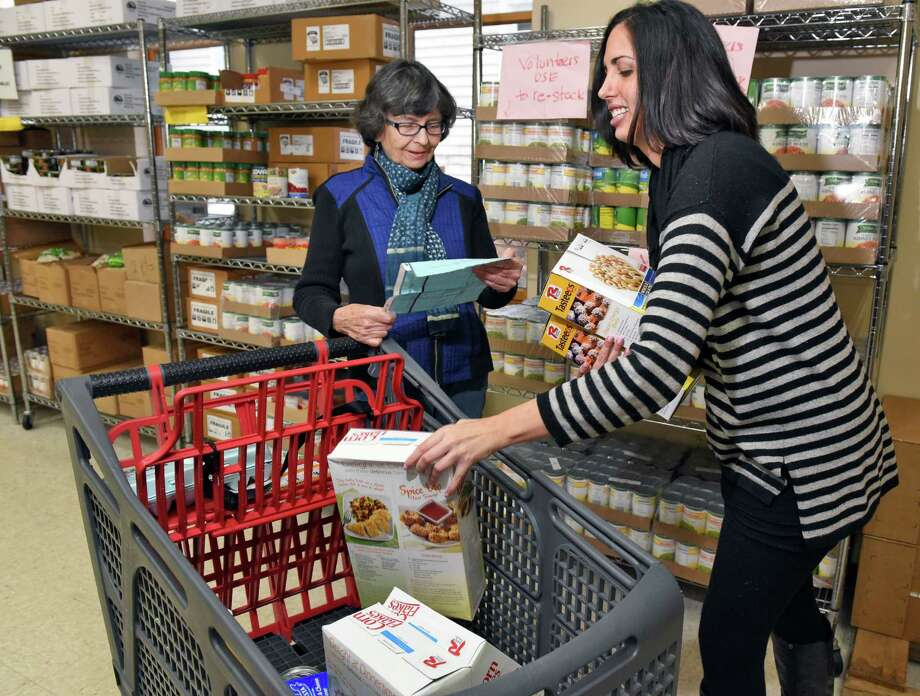 Volunteers Claire Malone,left, of Delmar and UAlbany grad student Jaime Coffino restock shelves at St VincentOs Parish Center's food pantry Friday Dec. 2, 2016 in Albany, NY.  (John Carl D'Annibale / Times Union) Photo: John Carl D'Annibale / 20039039A