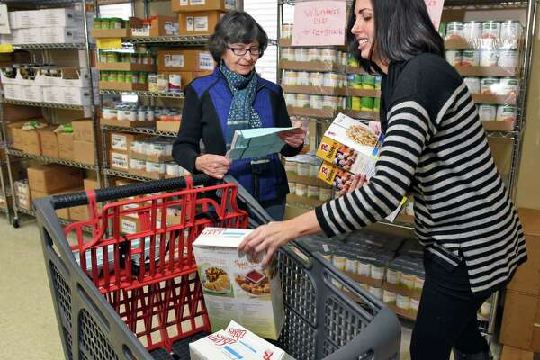 Volunteers Claire Malone,left, of Delmar and UAlbany grad student Jaime Coffino restock shelves at St VincentOs Parish Center's food pantry Friday Dec. 2, 2016 in Albany, NY. (John Carl D'Annibale / Times Union)