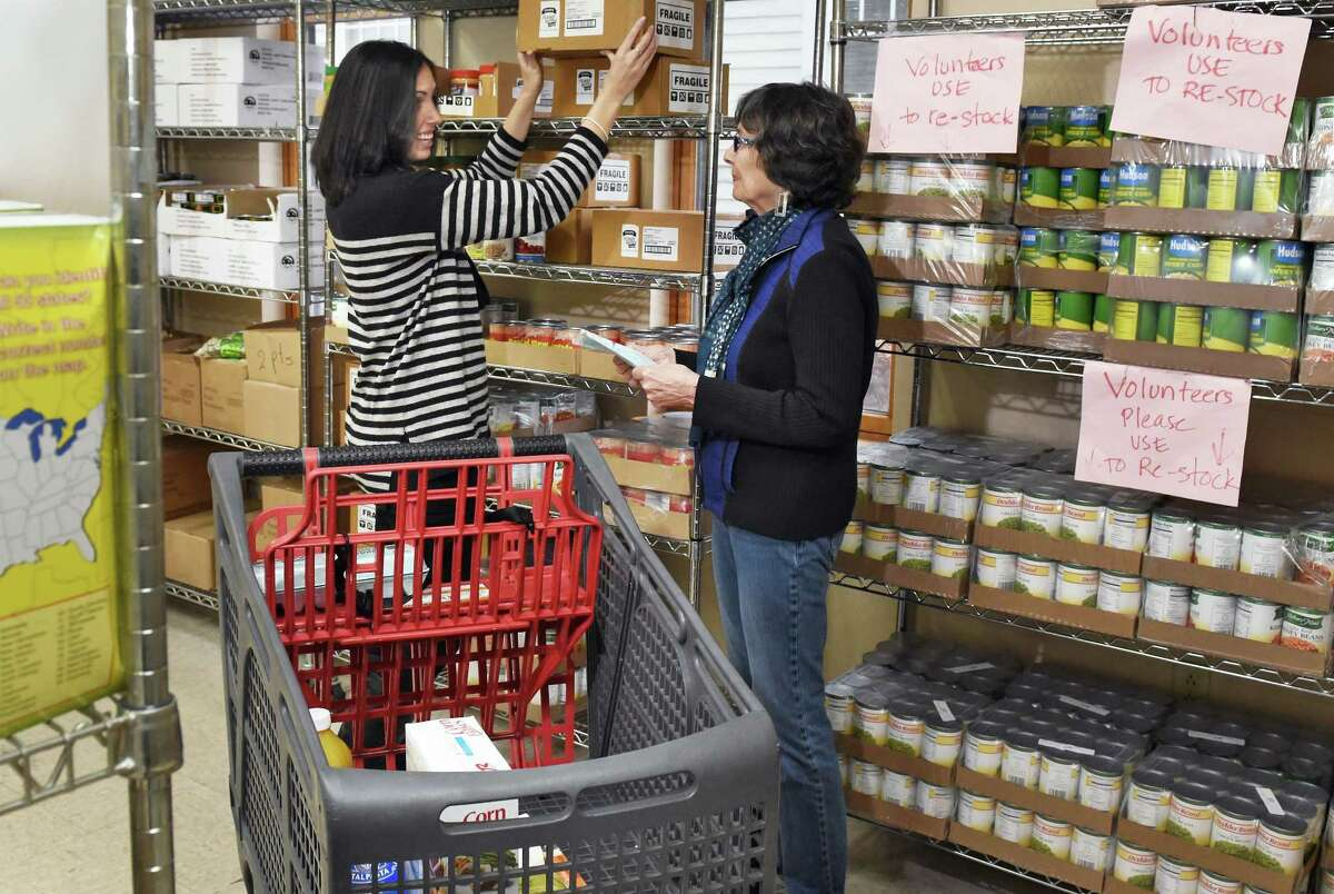 Volunteers, UAlbany grad student Jaime Coffino, left, and Claire Malone of Delmar restock shelves at St VincentOs Parish Center's food pantry Friday Dec. 2, 2016 in Albany, NY. (John Carl D'Annibale / Times Union)