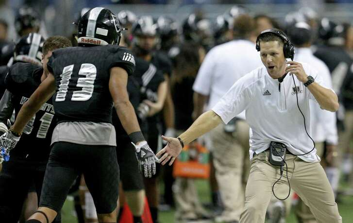 Steele's Onyx Smith celebrates with head coach Scott Lehnhoff after scoring a touchdown against Churchill during first half action of their Class 6A Division II state quarterfinal playoff game on Dec. 3, 2016 at the Alamodome.