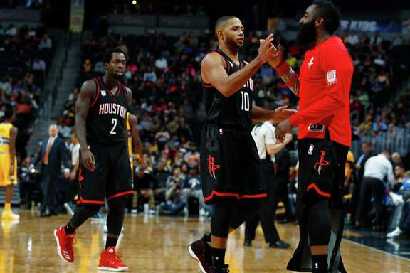 Rockets guard Eric Gordon, center, is congratulated by James Harden after scoring against the Nuggets in the second half of Friday's game. Gordon and Harden were two of seven Rockets who scored in double figures in the game.