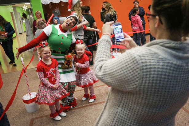 Willis resident Tammy Nichols, right, takes a photo of her recently adopted girls 3-year-old Karlee Holdren and 5-year-old Baylee Teston with volunteer Natalie Plaza, of Spring, during The Jingle Bell Christmas Party on Saturday, Dec. 3, 2016, at WoodsEdge Community Church.