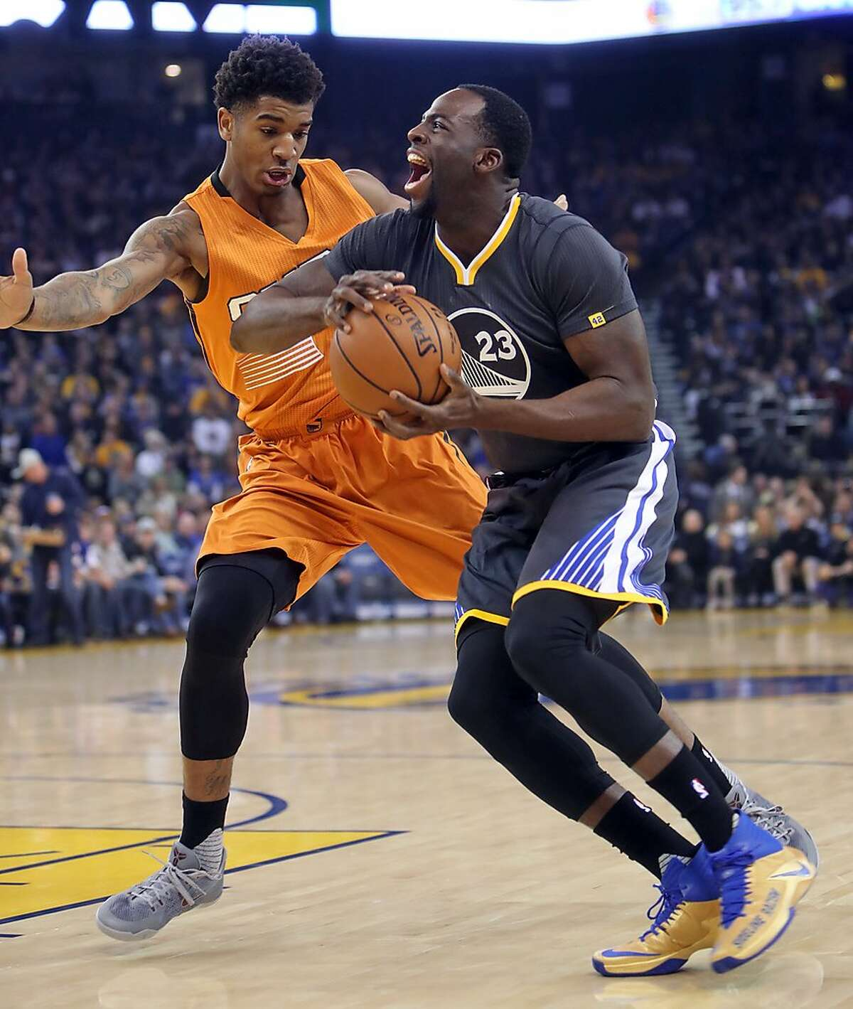 Golden State Warriors' Draymond Green is fouled by Phoenix Suns' Marquese Chriss in 1st quarter during NBA game at Oracle Arena in Oakland, Calif., on Saturday, December 3, 2016.