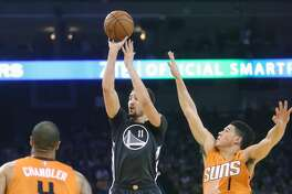 Golden State Warriors' Klay Thompson scores between Phoenix Suns' Tyson Chandler and Devin Booker in 1st quarter during NBA game at Oracle Arena in Oakland, Calif., on Saturday, December 3, 2016.