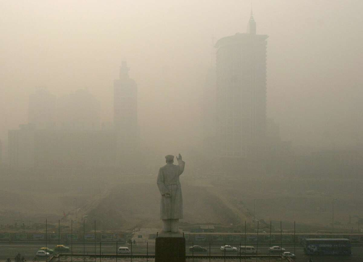 Heavy fog envelopes the Tianfu Plaza where the statue of Mao Zedong stands December 14, 2004 in Chengdu, Sichuan Province of China. The heaviest fog since winter has in some areas reduced visibility is to less than 10 meters (11 yards). (Photo by China Photos/Getty Images)