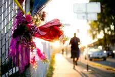 A jogger passes flowers at a makeshift memorial for victims of the Ghost Ship warehouse fire on Sunday, Dec. 4, 2016, in Oakland, Calif.