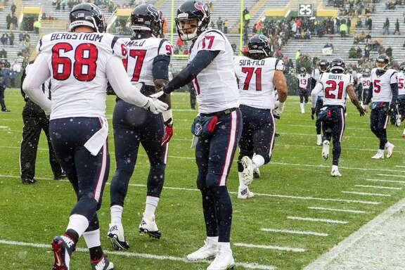 Houston Texans quarterback Brock Osweiler (17) slaps hands with center Tony Bergstrom (68) as the team runs onto the field for warm ups before an NFL football game against the Green Bay Packers at Lambeau Field on Sunday, Dec. 4, 2016, in Green Bay.