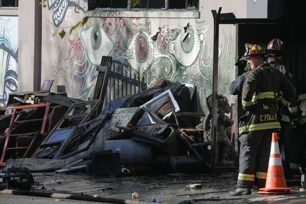 Firefighters work at the scene following an overnight fire that claimed the lives of at least 24 people at a warehouse in the Fruitvale neighborhood on December 3, 2016 in Oakland, California. The warehouse was hosting an electronic music party.