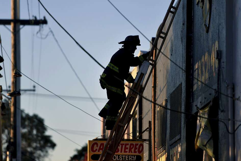 A firefighter climbs a ladder after a deadly fire at a warehouse rave party in Oakland, Calif., earlier in the morning on Dec. 3, 2016. (AP Photo/Josh Edelson)