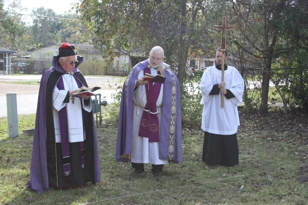 Father James Monroe (left) leads a service at the site of a new sanctuary for Holy Cross Anglican Church in Cleveland on Sunday, Nov. 27. The new building is on Fenner Street across from Croley Center.