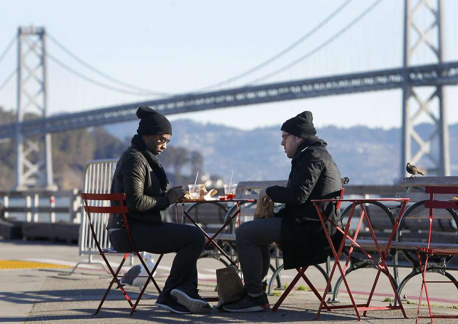 Temperatures will drop to about 30 degrees in the San Francisco Bay Area Wednesday morning, forecasters said. Richard Glover (left) and Stephen Eich wear wooly hats for an al fresco breakfast behind the Ferry Building in San Francisco, Calif. on Saturday, Dec. 26, 2015. Photo: Paul Chinn, The Chronicle