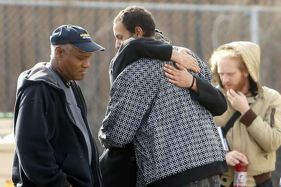 Two people embrace outside Alameda County Sheriff's Office on E. 12th Street in Oakland, Calif., on Sunday, December 4, 2016.