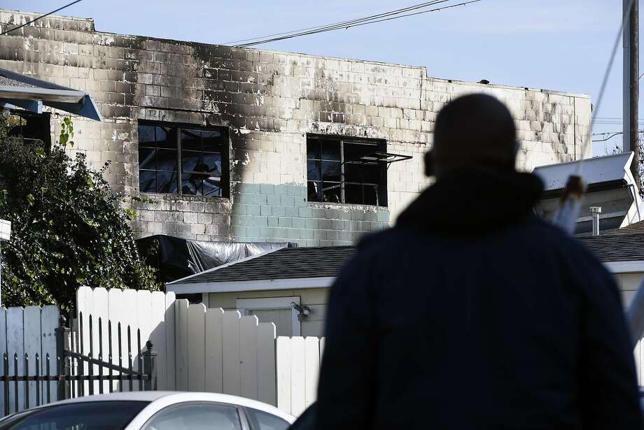 A person looks at the damage at the scene of the Ghost Ship artist warehouse fire in  Oakland, CA, on Sunday, December 4, 2016. Photo: Michael Short, Special To The Chronicle
