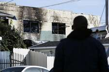 A person looks at the damage at the scene of the Ghost Ship artist warehouse fire in  Oakland, CA, on Sunday, December 4, 2016.