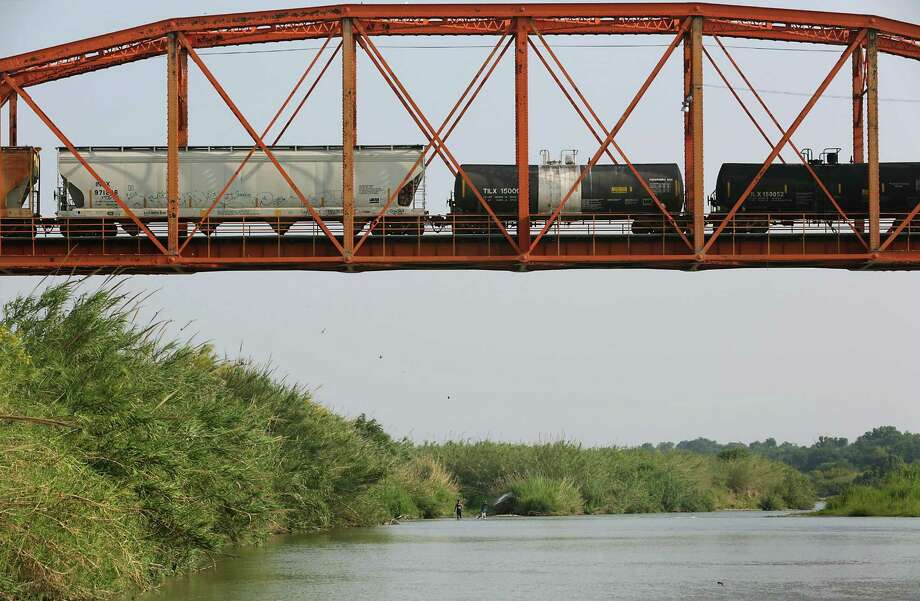 A train crosses the Rio Grande River into Piedras Negras, MX as fishermen cast their nets on Thursday, April 28, 2016. Photo: Bob Owen, Staff / San Antonio Express-News / San Antonio Express-News
