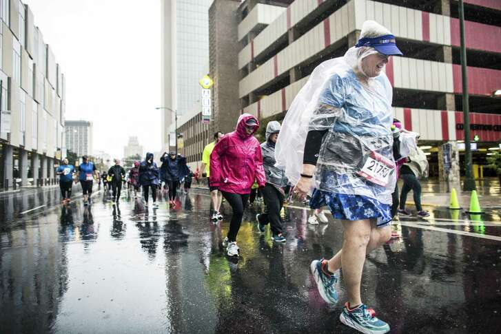 Runners continue on in the rain during the Humana Rock 'N' Roll Marathon in San Antonio, Texas on Sunday, December 4, 2016.