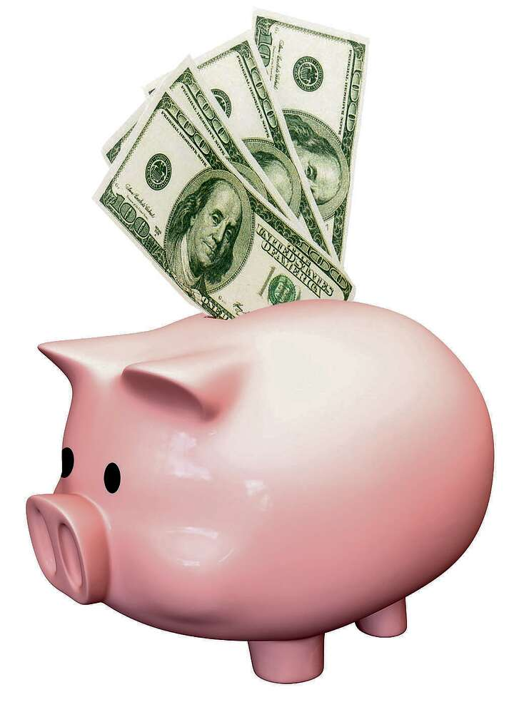 A pink ceramic piggy bank with a gold coin with a clock face design on it being deposited on an isolated background