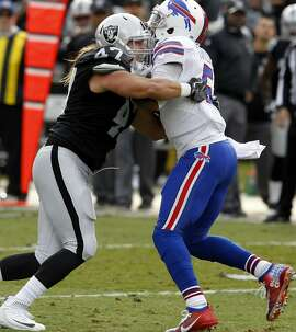 The Raiders James Cowser (47) sacks Bills quarterback Tyrod Taylor in the first quarter. The Oakland Raiders host the Buffalo Bills Sunday December 4, 2016 in Oakland, California.