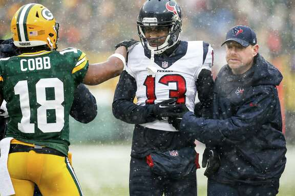 Houston Texans wide receiver Braxton Miller (13) is consoled by Green Bay Packers wide receiver Randall Cobb (18) as Miller leaves the field with trainer Geoff Kaplan after suffering an injury during the second quarter of an NFL football game at Lambeau Field on Sunday, Dec. 4, 2016, in Green Bay.