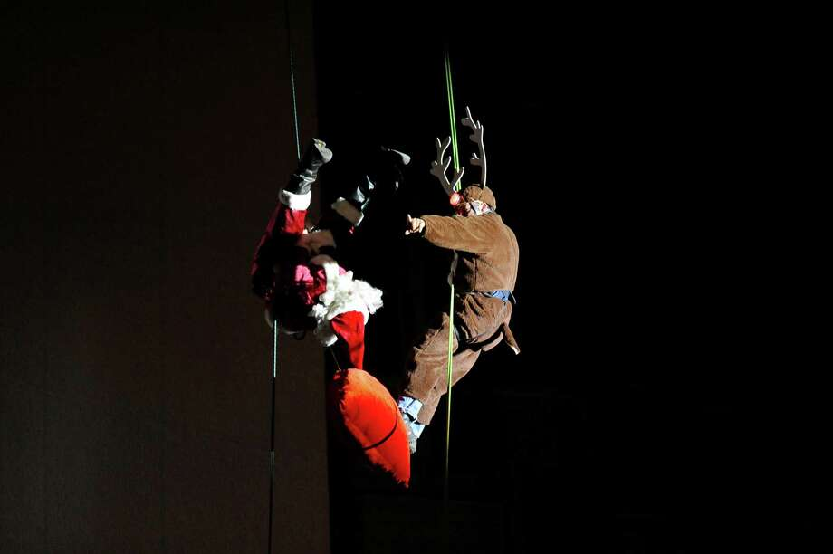 Brian VanOrsdel, as Santa, does a backflip in front of Ron Markey, as Rudolph, while rappelling down the Landmark Building during the 2016 Heights & Lights Rappel in Stamford, Conn. on Sunday, Dec. 4, 2016. Photo: Michael Cummo, Hearst Connecticut Media / Stamford Advocate