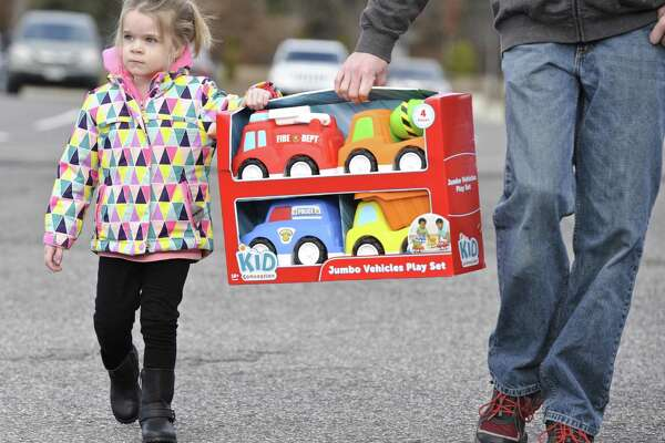"Madyson Colville, 2, of New Milford, gets a helping hand from her father, Josh Colville, carrying a toy to donate to the New Milford Police Department's  ""Stuff A Cruiser"" toy drive on Saturday. December 3, 2016, in New Milford, Conn."