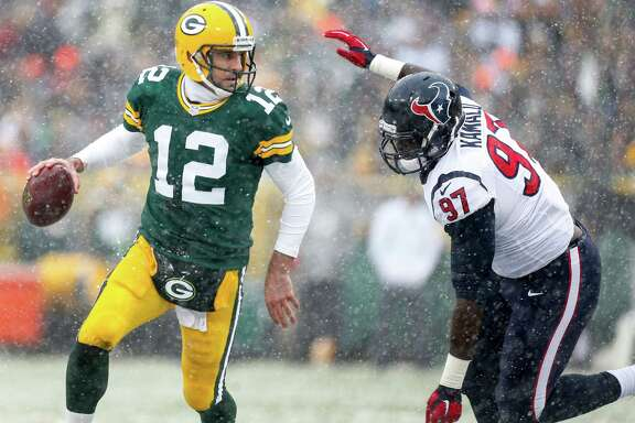 Packers quarterback Aaron Rodgers (12) eludes the pressure of the Texans' Ufomba Kamalu during the second quarter, a scene that was a familiar sight for several Texans defenders Sunday.