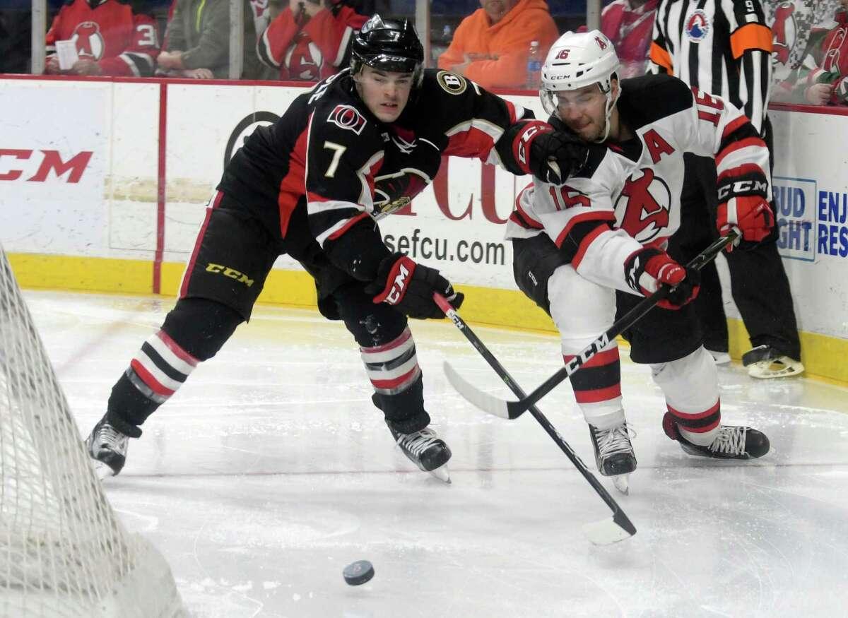 Chris Carlisle, left, with the Binghamton Senators and Ben Sexton, right, with the Albany Devils fight for control of the puck during their game on Sunday, Dec. 4, 2016, in Albany, N.Y. (Paul Buckowski / Times Union)