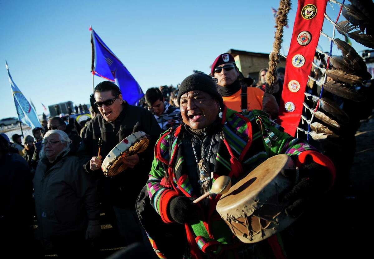 Dan Nanamkin, of the Colville Nez Perce Native American tribe in Nespelem, Wash., right, drums with a procession through the Oceti Sakowin camp after it was announced that the U.S. Army Corps of Engineers won't grant easement for the Dakota Access oil pipeline in Cannon Ball, N.D., Sunday, Dec. 4, 2016. (AP Photo/David Goldman) ORG XMIT: NDDG114