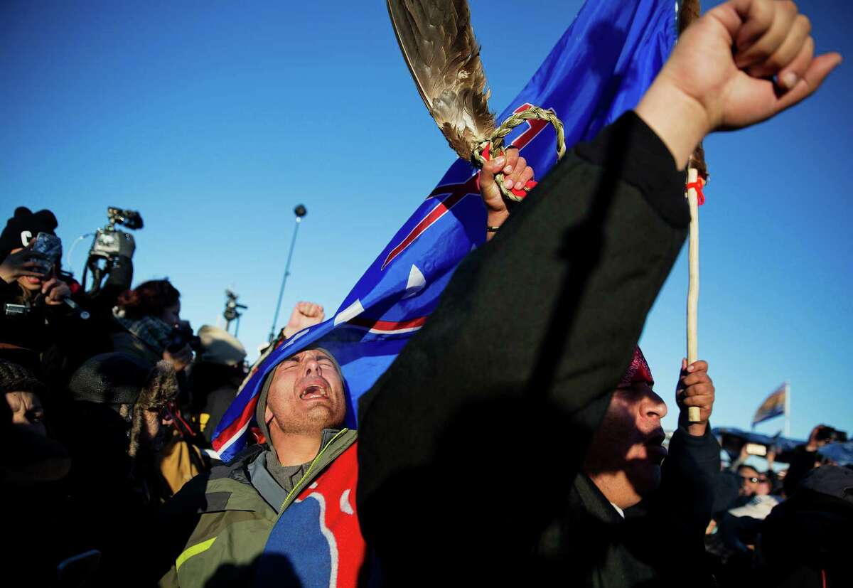 Members of a Native American drum procession celebrate at the Oceti Sakowin camp after it was announced that the U.S. Army Corps of Engineers won't grant easement for the Dakota Access oil pipeline in Cannon Ball, N.D., Sunday, Dec. 4, 2016. (AP Photo/David Goldman) ORG XMIT: NDDG115