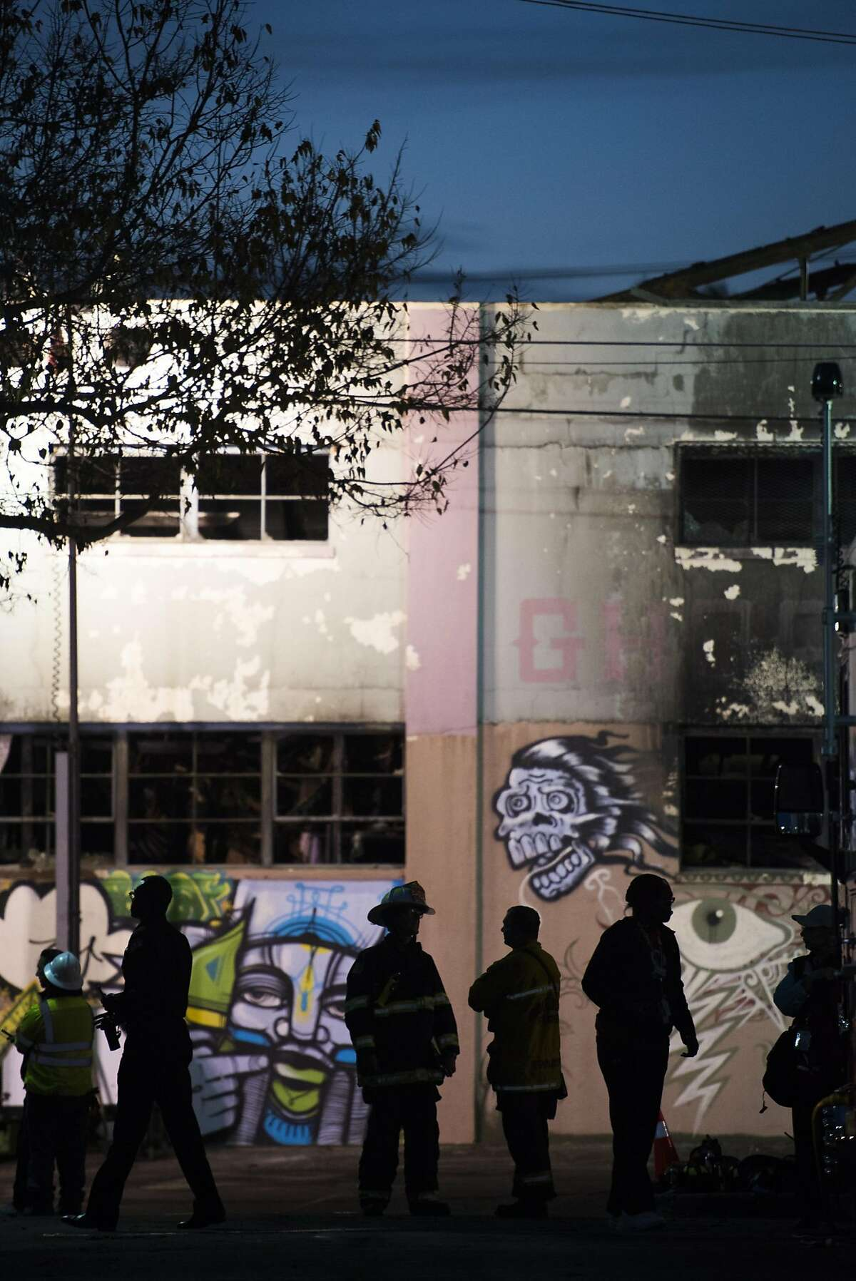 """Emergency personnel work at the scene of the Oakland warehouse fire on December 4, 2016 in Oakland, California. The fire, at an artist's warehouse known as the """"Ghost Ship,"""" began late on the evening of December 2nd, with 33 confirmed dead so far."""