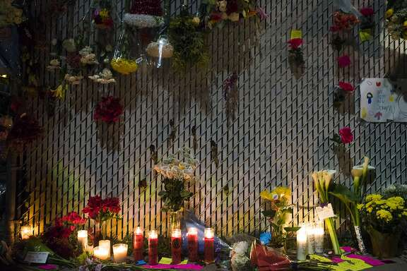 """Flowers, candles and notes left for victims of the Oakland warehouse fire are seen on the corner of 12th Street and 31st Avenue on December 4, 2016 in Oakland, California. The fire, at an artist's warehouse known as the """"Ghost Ship,"""" began late on the evening of December 2nd, with 33 confirmed dead so far."""