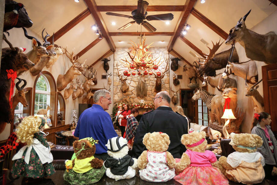 Salvation Army Maj. Don Wildish, right, chats with host Howard Crockett during the Salvation Army's Doll and Bear Tea event on Sunday, Dec. 4, 2016, in the trophy room of the Crockett home in Conroe. Photo: Michael Minasi, Staff / © 2016 Houston Chronicle
