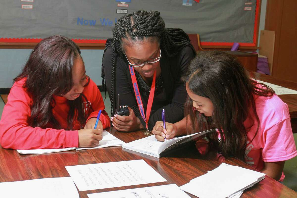 Talicia Stringer, center, of ProUnitas, works with students Dondrea Pugh, left, and Hannah Williams at the nonprofit's Kashmere Success Center.