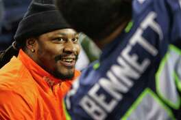 Former Seahawks running back Marshawn Lynch chats with Seahawks defensive lineman Michael Bennett on the sideline during the second half of the Seahawks game against the Carolina Panthers, Sunday, Dec. 4, 2016, at CenturyLink Field.