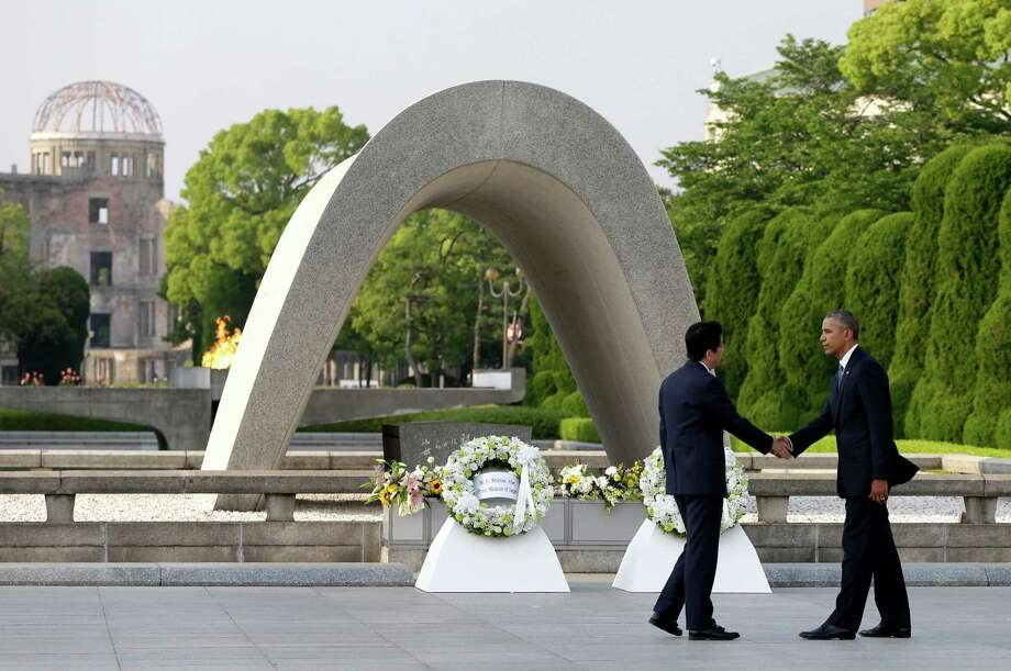 FILE - In this May 27, 2016 file photo, U.S. President Barack Obama, right, shakes hands with Japanese Prime Minister Shinzo Abe at Hiroshima Peace Memorial Park in Hiroshima, western Japan, as Obama became the first sitting U.S. president to visit the site of the world's first atomic bomb attack. Abe said Monday, Dec. 5, he will visit Pearl Harbor with Obama at the end of this month, becoming the first leader of his country to go to the U.S. Naval base in Hawaii that Japan attacked in 1941, propelling the United States into World War II. Atomic Bomb Dome is seen in the background. Photo: Carolyn Kaster, AP / Copyright 2016 The Associated Press. All rights reserved. This material may not be published, broadcast, rewritten or redistribu