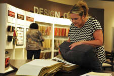 Ann Burns compares color choices to her existing couch while shopping at La-Z-Boy on Wednesday.  Photo taken Wednesday 11/30/16 Ryan Pelham/The Enterprise