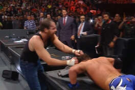 """FILE - WWE wrestler Dean Ambrose grabs the hair of AJ Styles during the main event of """"TLC: Tables, Ladders & Chairs"""" at the American Airlines Center in Dallas, Texas on Dec. 4, 2016. Styles pants tore, revealing his buttocks, during the match."""