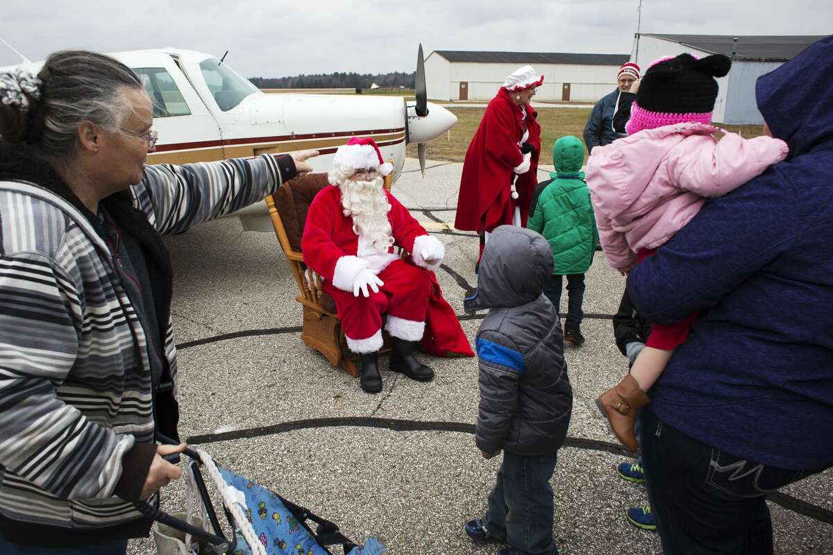 Santa sits next to an airplane while receiving a line of waiting children after arriving at Barstow Airport on Sunday.