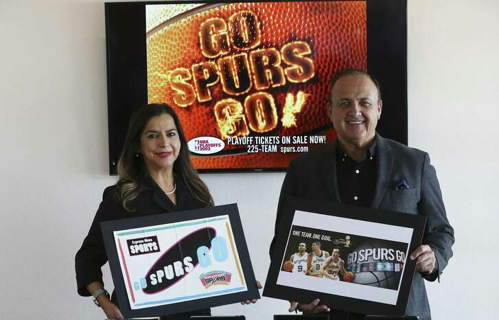 """Creative Civilization ad agency owner Al Aguilar and president/chief strategy officer Gisela Girard show off """"Go Spurs Go"""" placards they helped design."""