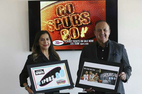"Creative Civilization ad agency owner Al Aguilar and president/chief strategy officer Gisela Girard show off ""Go Spurs Go"" placards they helped design."