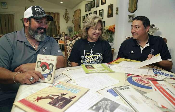 Chris (from left), Juanita and Adam Montalvo look over some Spurs memorabilia.