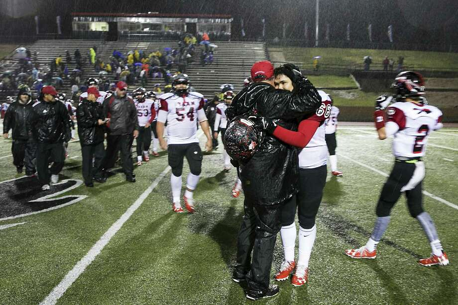 Mark Kirchhoff, the head coach of the Iraan High School Braves, embraces Steven Garlock, 17, following a win in Colorado City, Texas, on Dec. 2, 2016. Hours after an away-game victory, a bus full of Iraan Highs cheerleaders was involved in a rainy collision with an 18-wheeler, injuring many, including Garlock's mother, and killing his aunt, who served as the sponsor of the junior high cheerleaders. Photo: Ilana Panich-Linsman /New York Times / NYTNS