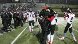 Mark Kirchhoff, the head coach of the Iraan High School Braves, embraces Steven Garlock, 17, following a win in Colorado City, Texas, Dec. 2, 2016. Hours after an away-game victory, a bus full of Iraan Highs cheerleaders was involved in a rainy collision with an 18-wheeler, injuring many, including Garlock's mother, and killing his aunt, who served as the sponsor of the junior high cheerleaders.