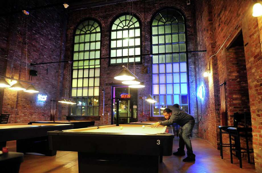 Co-owner Sean Gooden plays a game of pool at Four Corner Billiards L.L.C. on Bank Street in Bridgeport, Conn. on Thursday Nov. 30, 2016. The pool hall, which opened three weeks ago, was started by four correctional officers who work at Bridgeport Correctional Facility. The other owners besides Gooden include fellow correctional officers Ricky M. Pettway Jr, Wenroy Reid and Edgar Decena. Photo: Christian Abraham / Hearst Connecticut Media / Connecticut Post