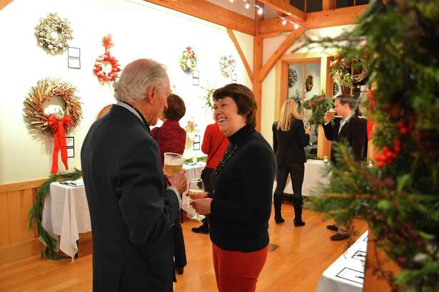 Chris Filmer chats with Caroline Burke, both of Darien, at the Festival of Wreaths, a holiday fundraiser held at the Darien Nature Center Friday, Dec. 2, 2016, in Darien, Conn.