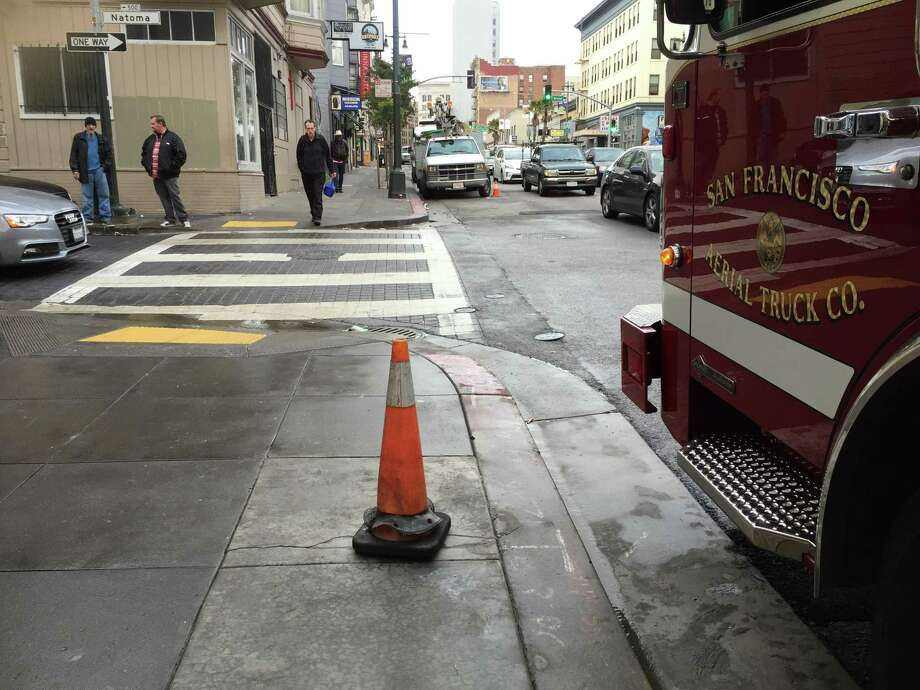 A driver crashed into a fire hydrant Monday morning on Sixth and Minna streets, which subsequently caused water damage to a homeless shelter nearby, officials said. The orange cone replaces the spot where the fire hydrant used to be. Photo: Sarah Ravani / The Chronicle / Sarah Ravani / The Chronicle