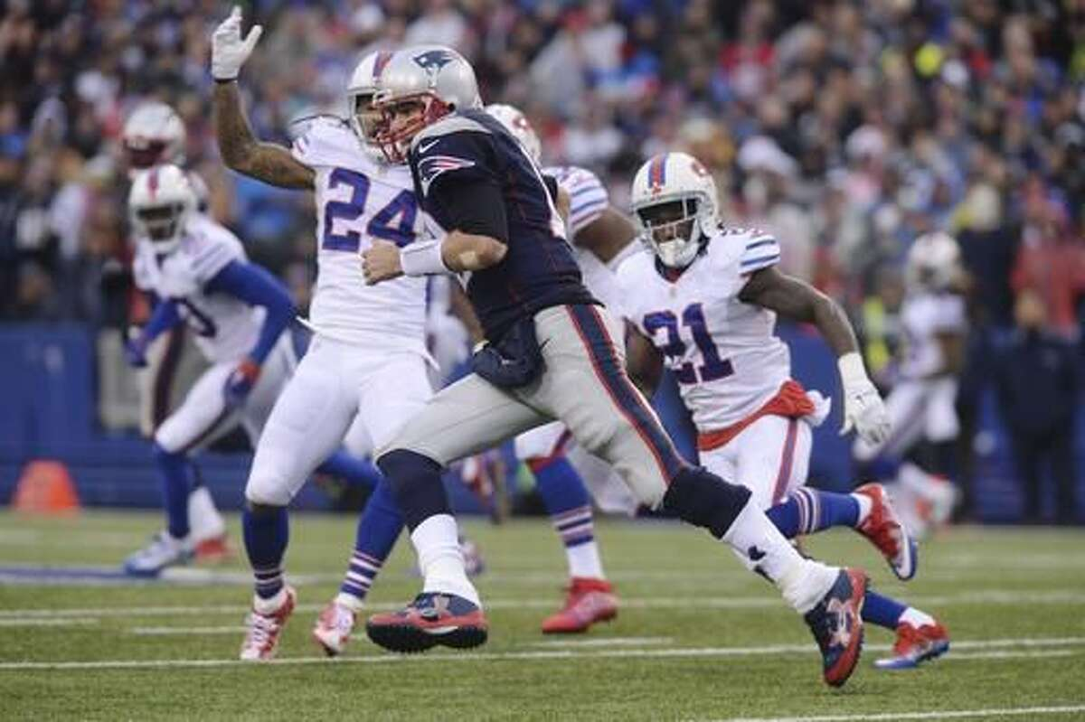 New England Patriots quarterback Tom Brady (12) rushes past Buffalo Bills' Stephon Gilmore (24) and Nickell Robey-Coleman (21) during the second half of an NFL football game Sunday, Oct. 30, 2016, in Orchard Park, N.Y. (AP Photo/Adrian Kraus)